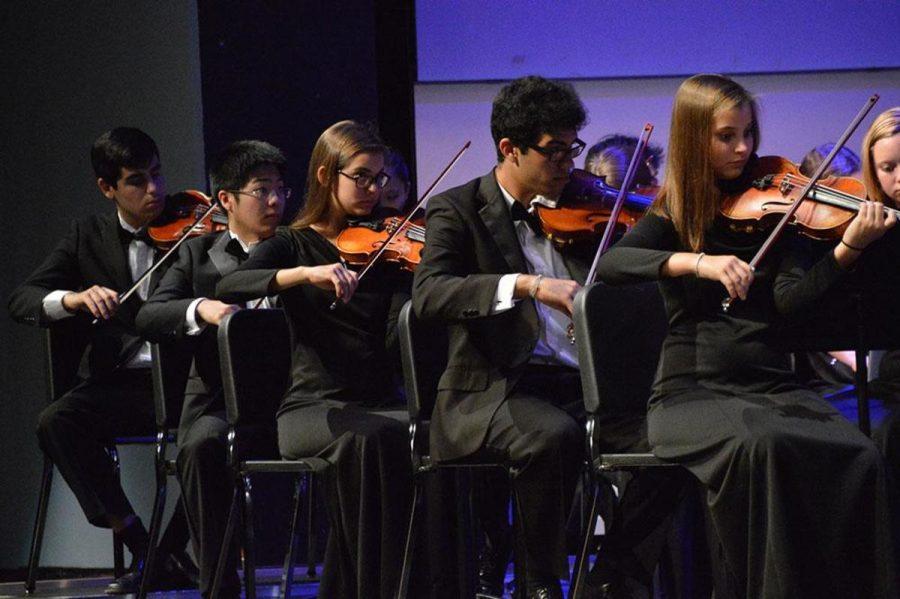 Strings seniors Felipe Bomeny, Taisuke Yasudam, Robin Tozzie, strings junior Yuri Santos  and strings senior Rebecca Tozzie play in the violin section during the concert.