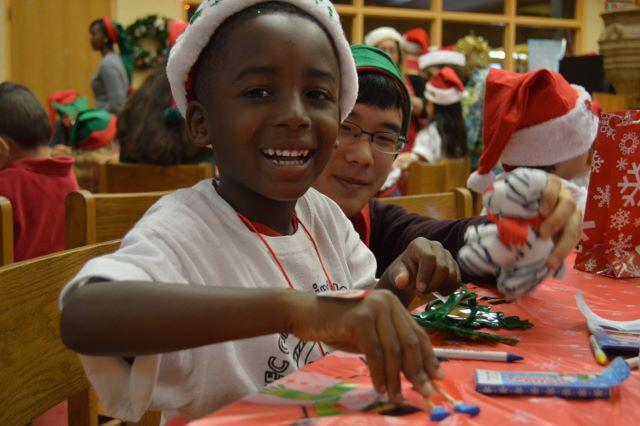 (L-R) Canal Point Elementary student and band junior Minh Ton express their jolly spirits while playing with gingerbread man toys.