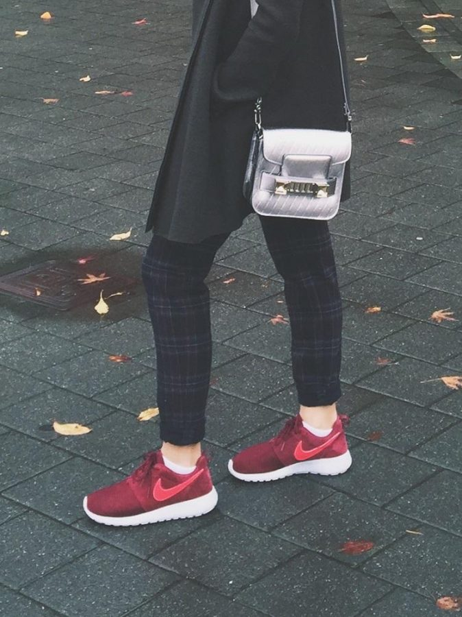 Gabi Passos in her Roshe Runs. Paired with plaid pants a silver cross body bag and gray coat.
