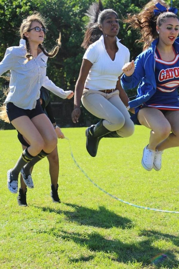 Communications freshman Chantel Mcmillan (l-r), sophomore, and dance junior Olivia Izenwasser jumping in the Quadruple Dutch event today during lunch.
