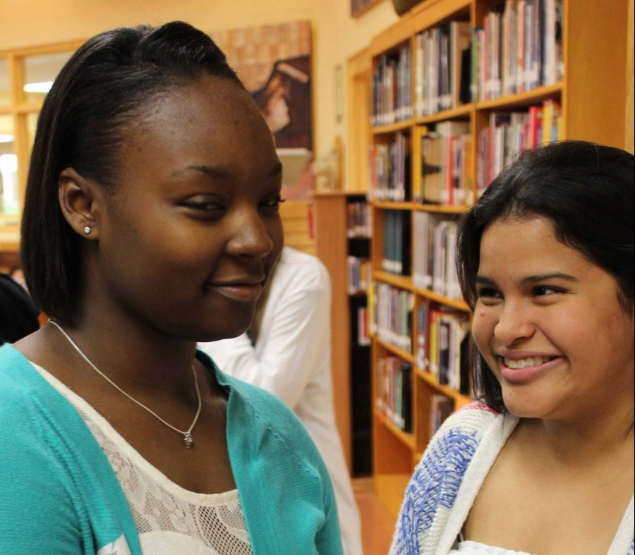 """(L-R) Strings juniors Kevonna Shuford and Maria Fernandez laugh while discussing the good and bad of journalism. """"Journalism [reminds me of] being sneaky and deceptive because the news can be altered slightly depending on the source. The stuff that we hear is normally a little sugarcoated or exaggerated,"""" Shuford said.  """"Journalism reminds me of the truth and exploited pieces of the truth because [journalism] may be completely accurate and a good portion of journalism is that way. However, there is a lot of yellow journalism going on now. Many events are exaggerated and unreliable sources nowadays take little portions of the truth and twist them for public appeal,""""  Fernandez said."""