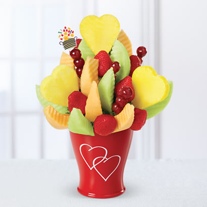 This edible fruit includes grapes, honeydew wedges, kale, strawberries, and pineapple hearts to complete a healthy Valentine's Day gift.