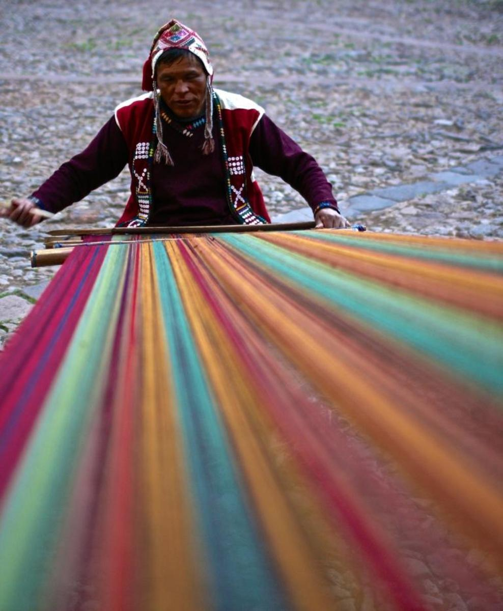 A weaver makes a multicolored blanket in Cuzco using traditional tools and methods. Many people in the rural areas of Peru still make their clothes by hand using use hand-dyed alpaca wool. During winter, the temperature in the Andes gets as low as 32 degrees F.