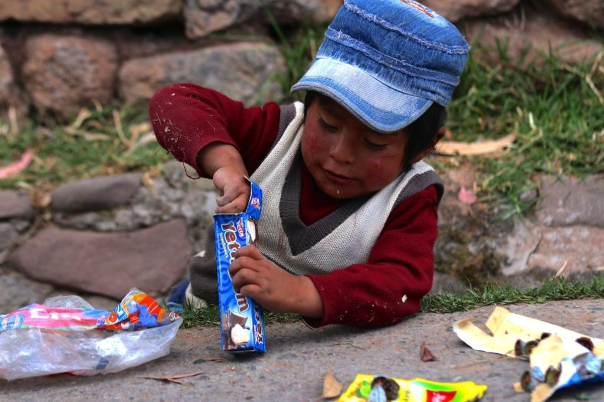 A child plays with discarded packaging in a ditch beside his parent's food cart. Many people in Cuzco rely on tourism for their income. Peru has had steady economic growth in metropolitan areas but in more rural outskirts.