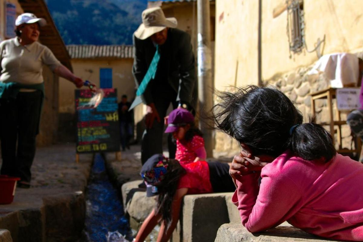 Children watched by their grandparents play by one of the irrigation channels in the city of Ollantaytambo. These channels were built by the Incas to bring fresh water into their cities, but now serve as little more than miniature attractions.