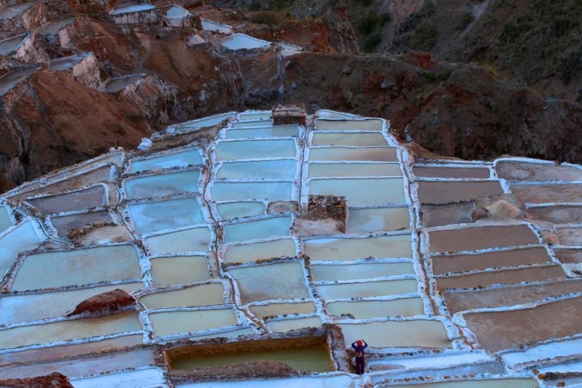 Salt beds like these in the city of Maras have been used since pre-Inca times as primary source of salt for the people living in the Andes.  Underground streams flow through salt deposits deep within the Andes Mountains, carrying out water with a much higher salinity than ocean water. The streams are feed into beds, which are used by families in the community to harvest salt for sale.