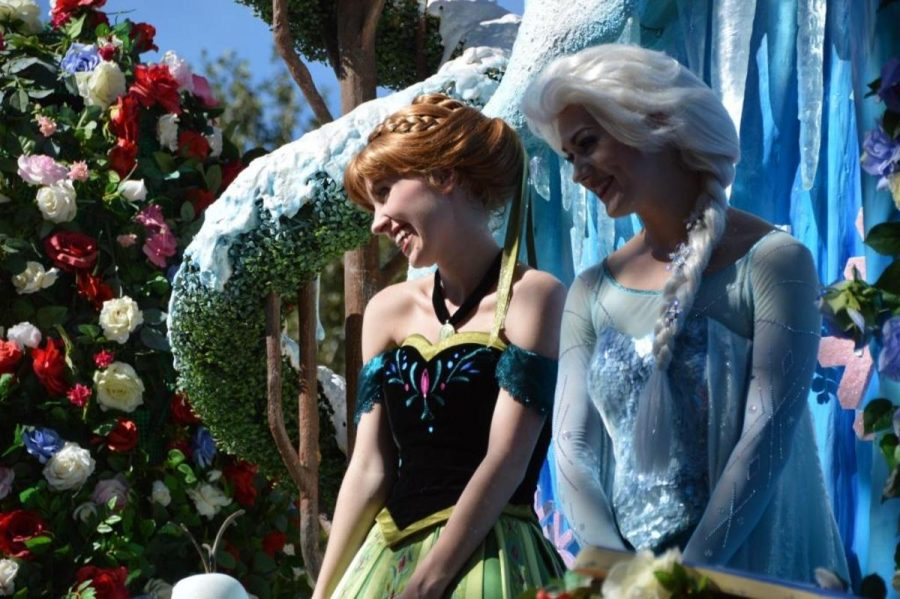 Frozen characters Ana and Elsa smile to Disney-goers at a parade