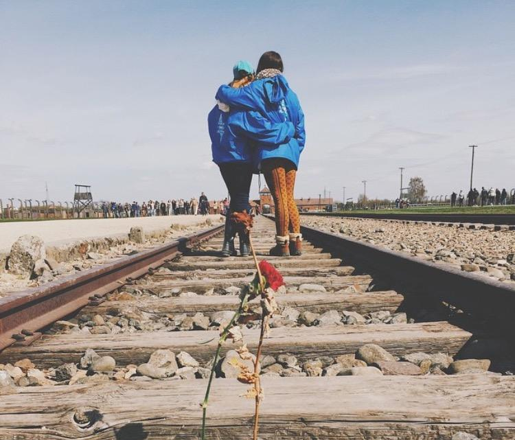 Theatre senior Amanda Shore (left) walks over the train tracks that marked the lives lost during the holocaust.