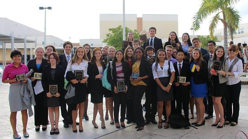 Members of the debate team pose with their awards.