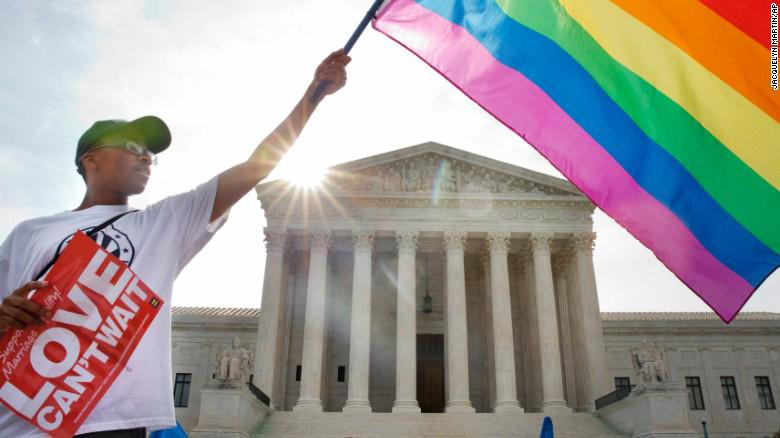 A protester supporting same-sex marriage stands outside the Supreme Court as Justices deliberate Obergefell v. Hodges. In a 5-4 decision, the Court legalized same-sex marriages in all states.