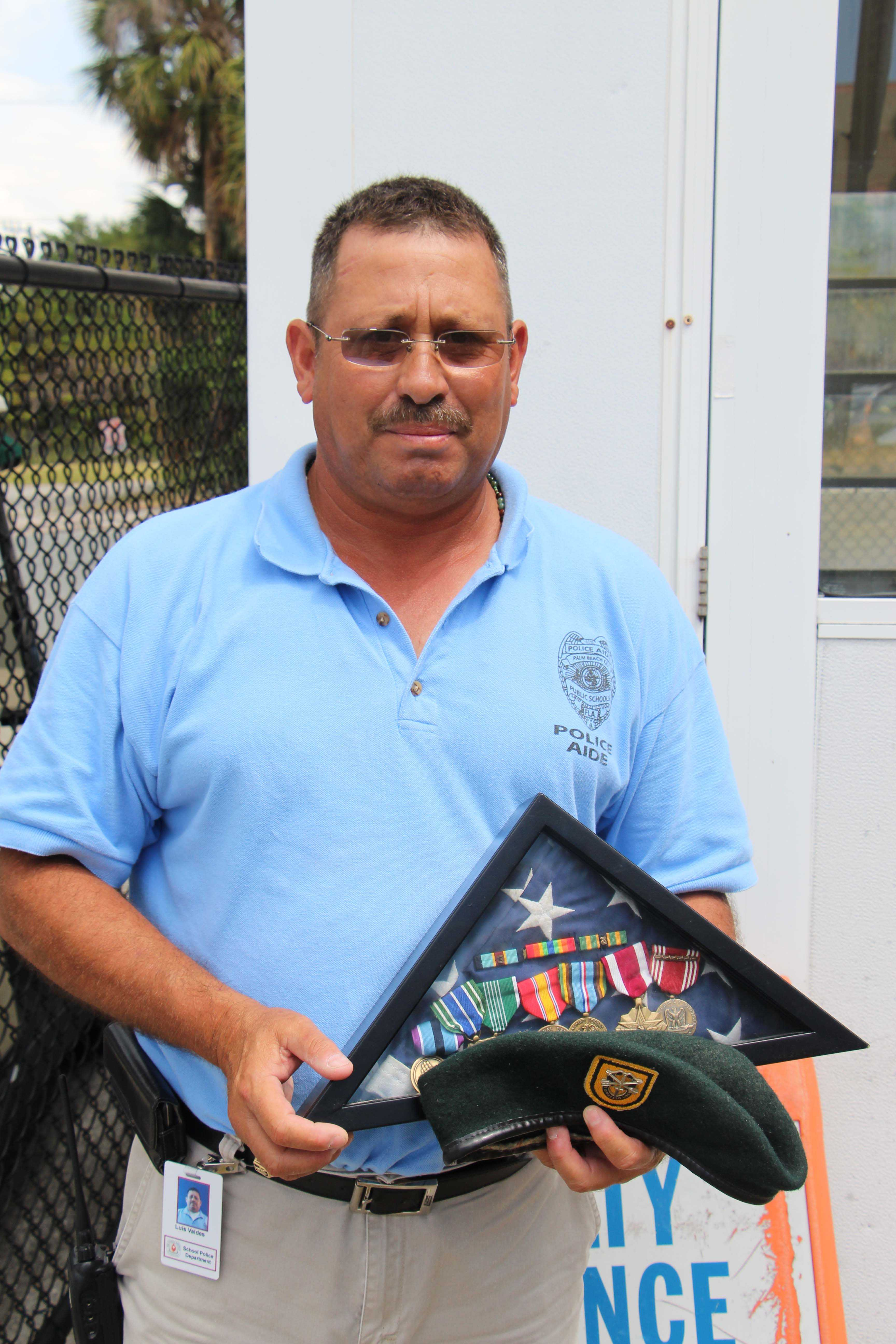Officer Louis Valdez stands with medals he has received throughout his military service.