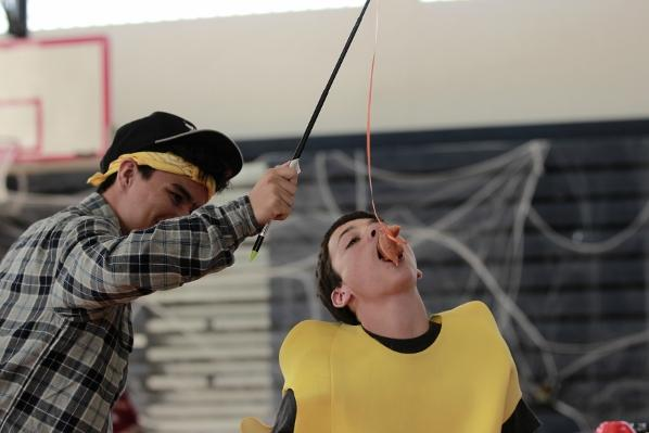 Strings junior Jorge Plaza dangles a doughnut for band freshman Mark Silver as he competes in the Fall Festival's doughnut eating race during lunch on Friday, Oct. 30.