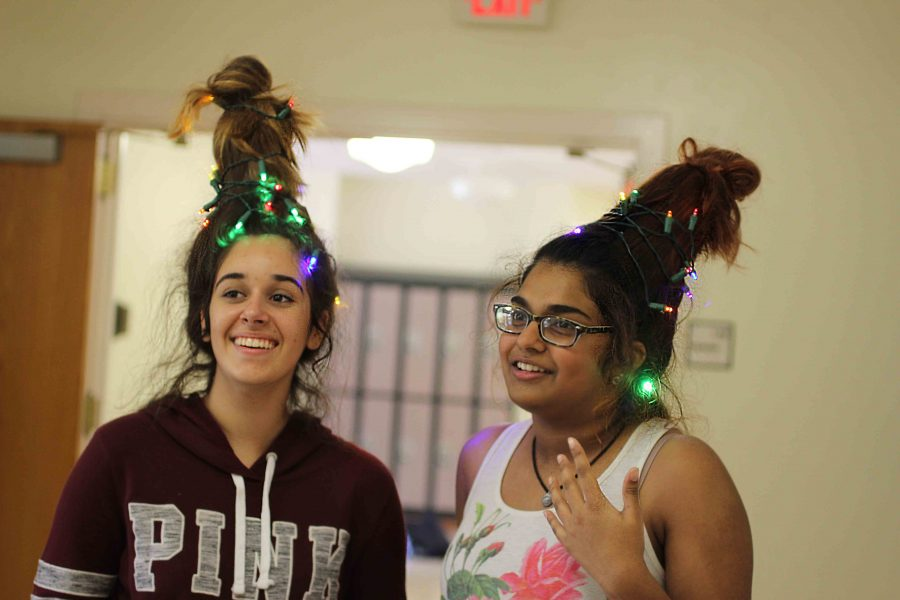 (L-R) Communications freshmen Madelyn Perera and Kavyasree Chigurupati adorn Christmas light updos to celebrate the beginning of the holiday season.