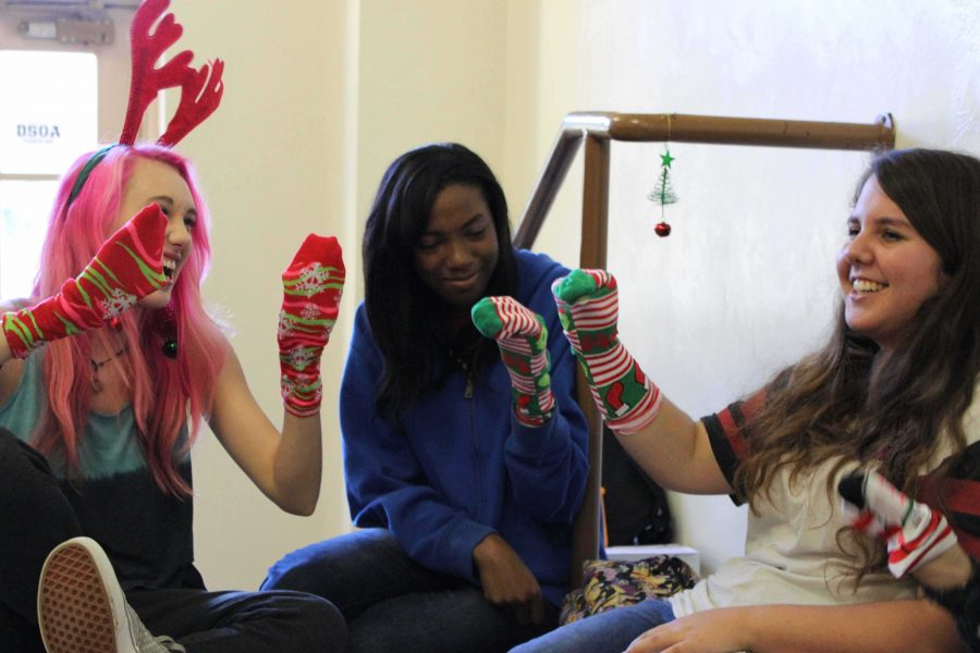 (L-R) Communications seniors Rachel Glismann, Destiny Washington and Lauren Punales sing Christmas carols and play with Christmas socks during lunch.