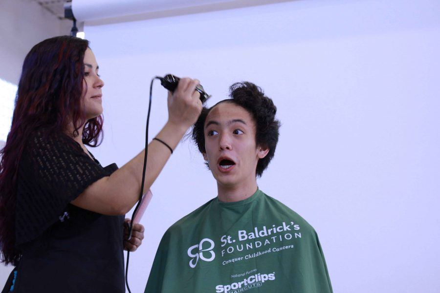 Theatre sophomore Evan Kwon shaves his head to raise awareness for childhood cancer at St.Baldrick's shaving and fundraising event. The club raised over $7,500 for kids battling cancer.