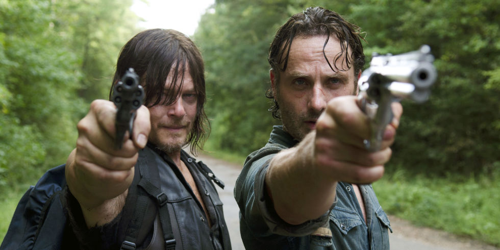 Daryl and Rick hold their weapons to a newly encountered survivor