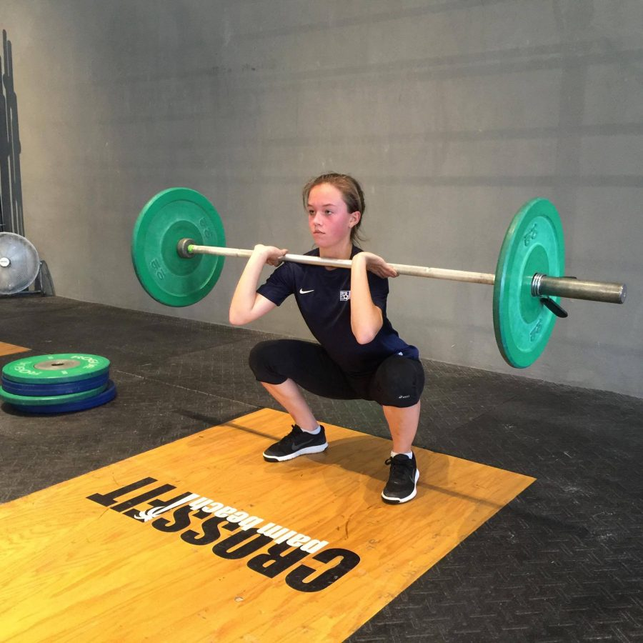 Theatre junior Ashton Royal performs a push press and a front squat at her Crossfit gym. Royal typically works out two to three times a week.