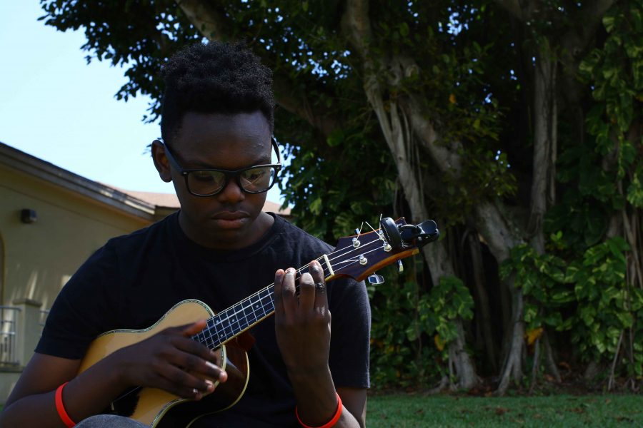 Visual freshman Jeremy Greenly plays his ukulele in the shade of the banyan tree on Freshman Hill.