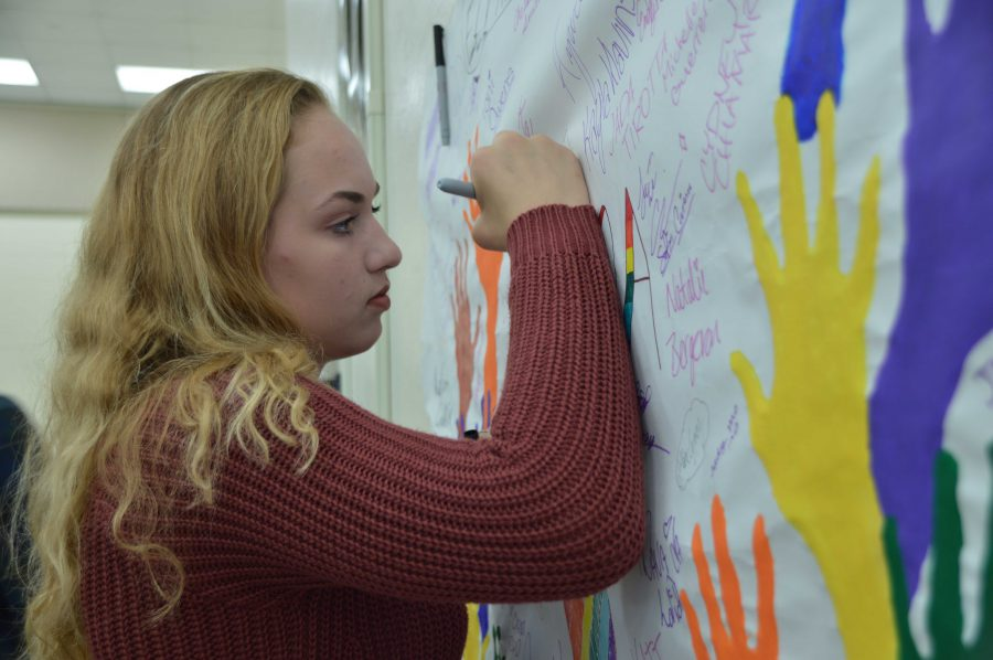 Dance sophomore Emily Sutterfield signs a decorative banner in solidarity for LGBTQ+ rights. April 15 is the international Day of Silence when students across the world refrain from speaking for 24 hours to raise awareness for the LGBTQ+ community.