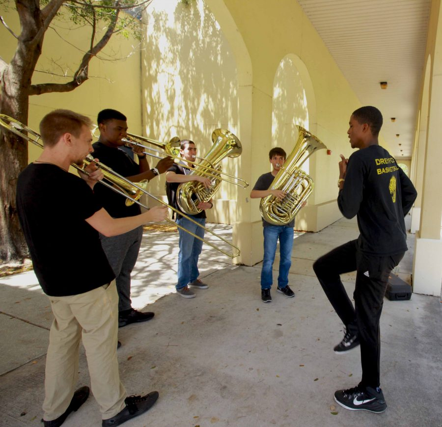 (L-R) Band senior Tyren Woods dances to music made by band juniors Kyle Virtue, Yoel Lugones, Kaleb Marshall and senior Triton Payne. The four practiced outside building 7.