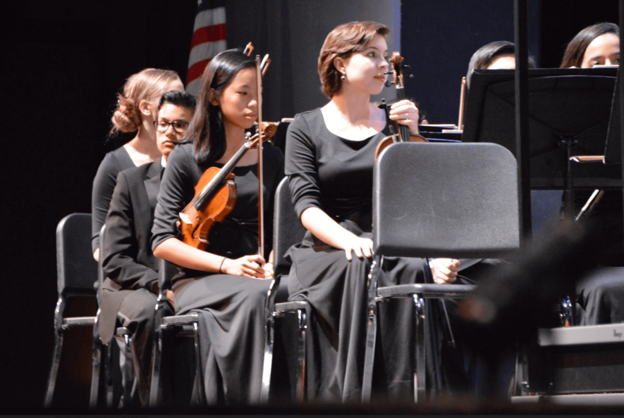 """(Front to Back:) Strings senior Kasia Leavitt, strings freshman Seoyoung Kwon, and strings sophomore Nicholas Abrahams play """"Hebrides Overture"""" at the last Philharmonic Orchestra of the year."""