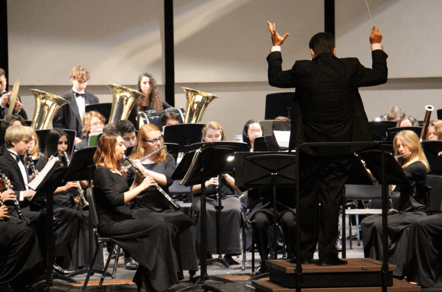"""Band director Evan Rogovin stands with his back to the crowd as he conducts the Symphonic Band's performance of """"Undertow,"""" a number by John Mackey."""