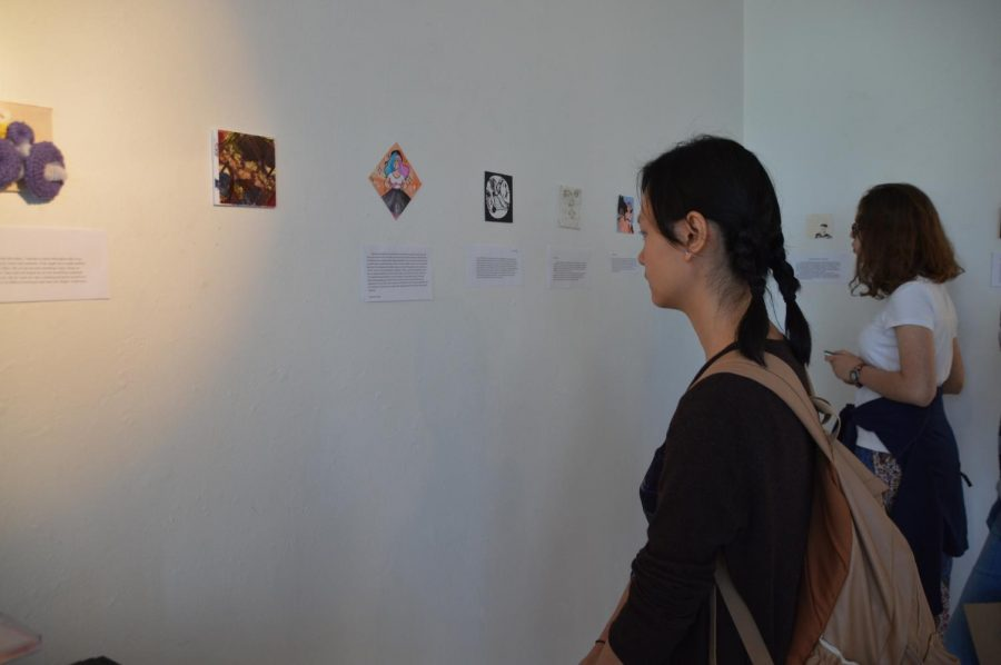 Piano senior Catherine Zeng scans the walls of the building 9 art gallery, looking at the individual senior portraits.