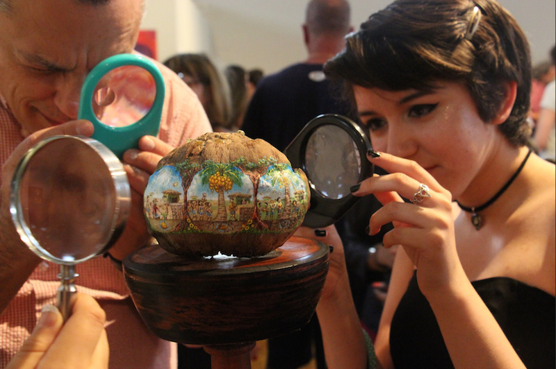 Visual senior Jailine Cano admires a piece by visual senior Palmer Crippen. The piece was made of a coconut, in which a story was painted in remarkably small detail. The details were so minuscule that one had to look through a microscope to grasp the whole story.