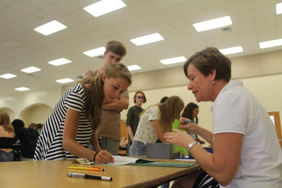 Communications sophomore Elizabeth White purchases her locker for the year from volunteer, Mrs. Fullop in the cafeteria.