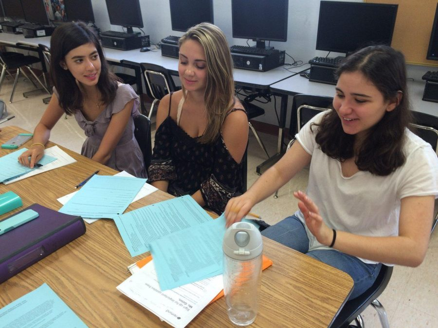Communications juniors Ashley Brundage (L-R), Morgan Scott and Ruby Rosenthal flip through their Muse syllabi in preparation for the upcoming school year. The Muse staff members are excited to bring new stories to the new school year.