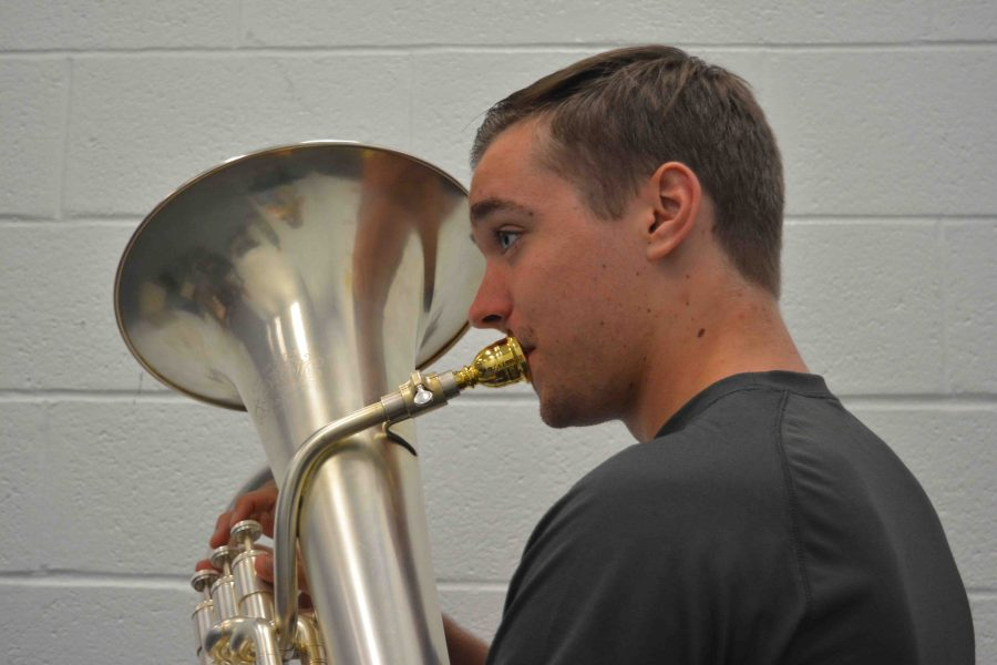 Band junior Spencer Edwards plays his euphonium in a music room during lunch.