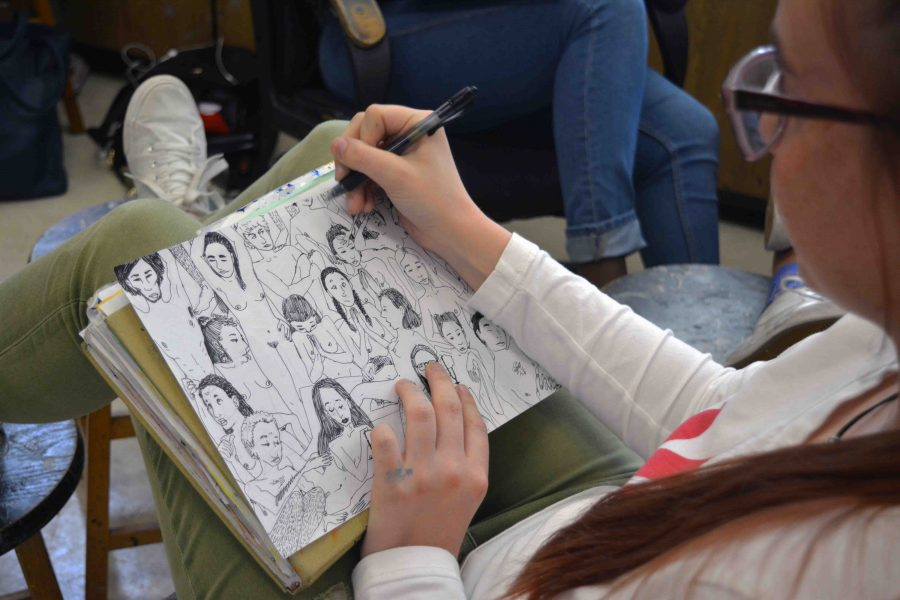 "Visual junior Megan Hostetler works on one of her many themed art pieces that emphasize and illustrate the human body from a unique perspective. ""My art deals with the juxtaposition of expressing sexuality within a religious society,"" Hostetler said."