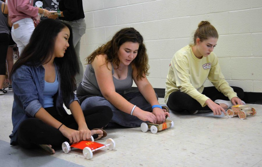 """(L-R) Band junior Lihn Ton, communications junior Dylan Pollak, and dance junior Pia Kresse practice racing the cars they built for physics class using only a rubber band and McDonald's trash. """"The process of creating the car was tedious, but it was rewarding to see my hard work pay off when it [the car] actually worked,"""" Ton said."""