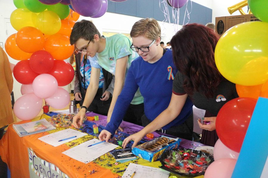 (L-R) Communications senior, Matthew Nadel, communications sophomore, Eli Anderson and theatre senior, Suzanne Litwinka prepare The Gender and Sexuality Alliance Club's table for Club Rush.