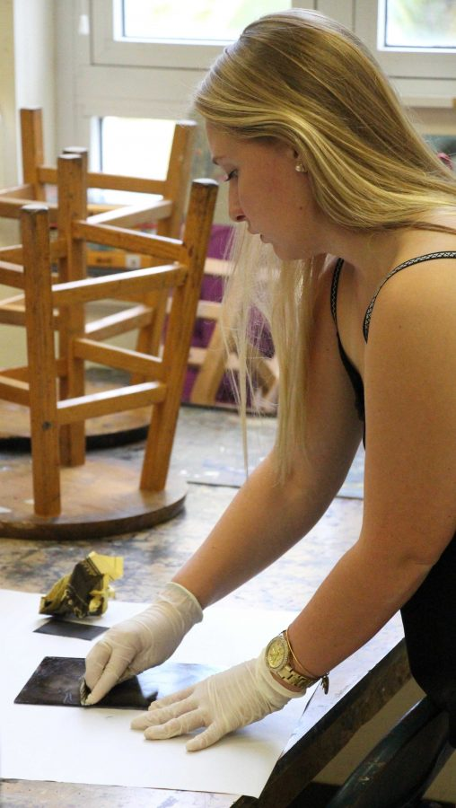 Communications senior, Stephanie Hartman prepares her drypoint etching for a test print during AP 2-D.