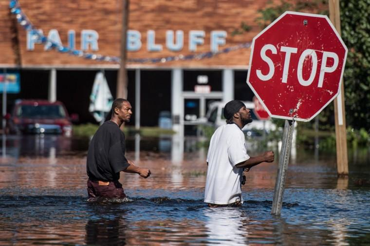Two men walk through a flooded street caused by remnants of Hurricane Matthew on October 11, 2016 in Fair Bluff, North Carolina. Thousands of homes have been damaged in North Carolina as a result of the storm and many are still under threat of flooding.