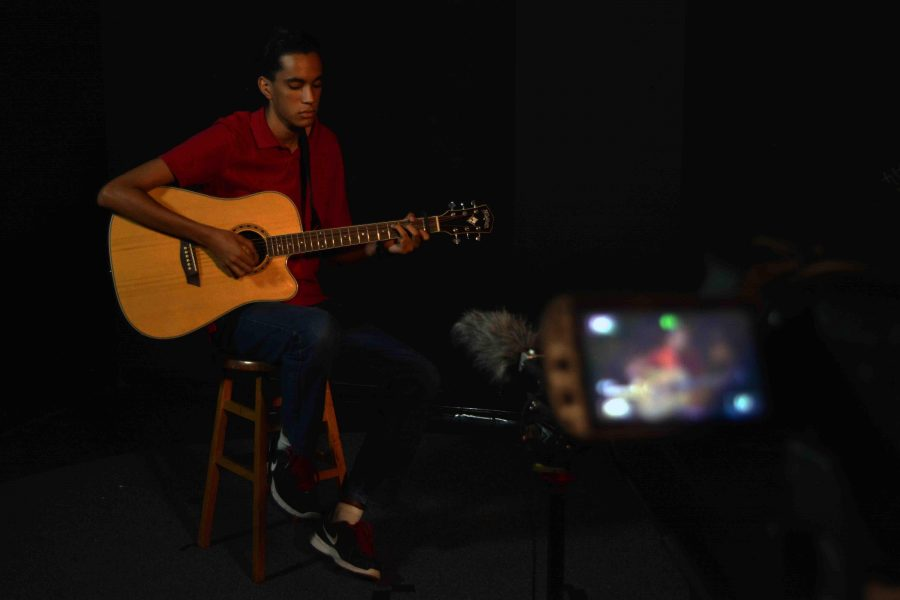 Theatre senior Keshin Martin plays and sings an original song while communications majors film him for his music video during lunch.
