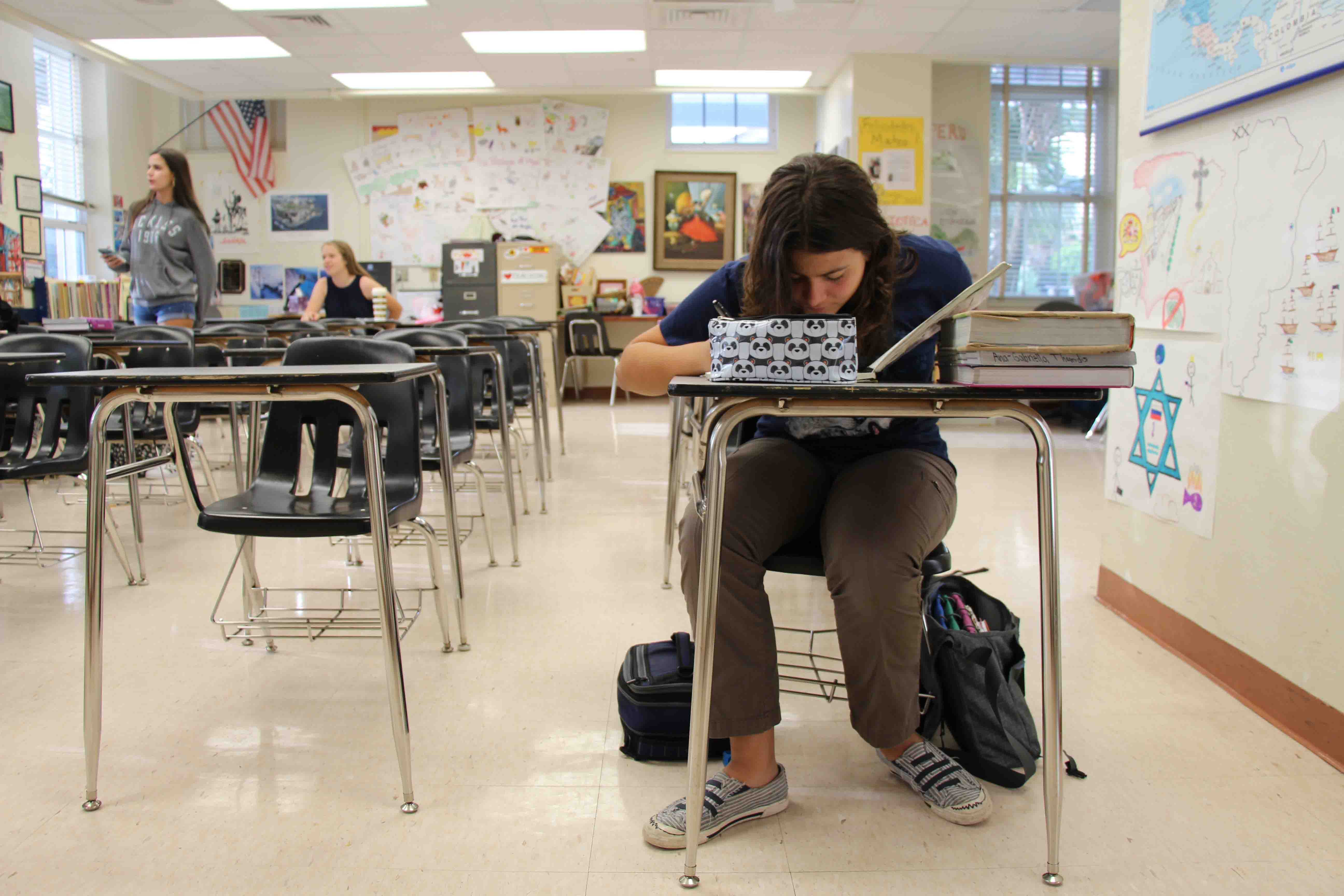 Visual freshman Gabi Thomadis sits at her desk and sketches in her sketchbook in a nearly empty classroom. Many students stayed home today so that they could help their families prepare for the hurricane possibly heading towards Florida.