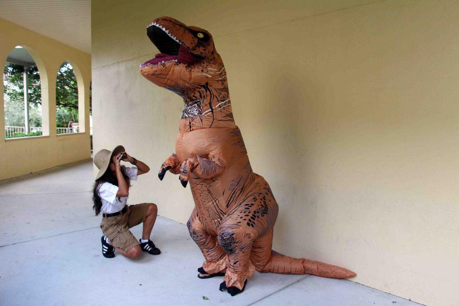 Visual senior Gleinys Martinez (left) stares up through binoculars at  communications senior Daniel Kaufman, clad in a dinosaur suit, on Safari Day.