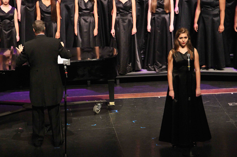 """Vocal junior Ashlyn Taylor performs a solo during """"Wood River,"""" by Willi Zwozdesky, while vocal dean Ken Taylor directs the chorus to sing background notes."""