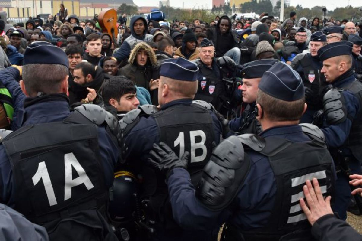 "French police control a crowd of migrants during the three-day process to clear the migrant camp, or the ""Jungle,"" in Calais."