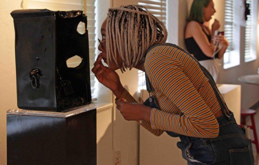 Digital junior Ashley Prather looks at an art sculpture during the Grosstober Art Showcase on Oct. 27.