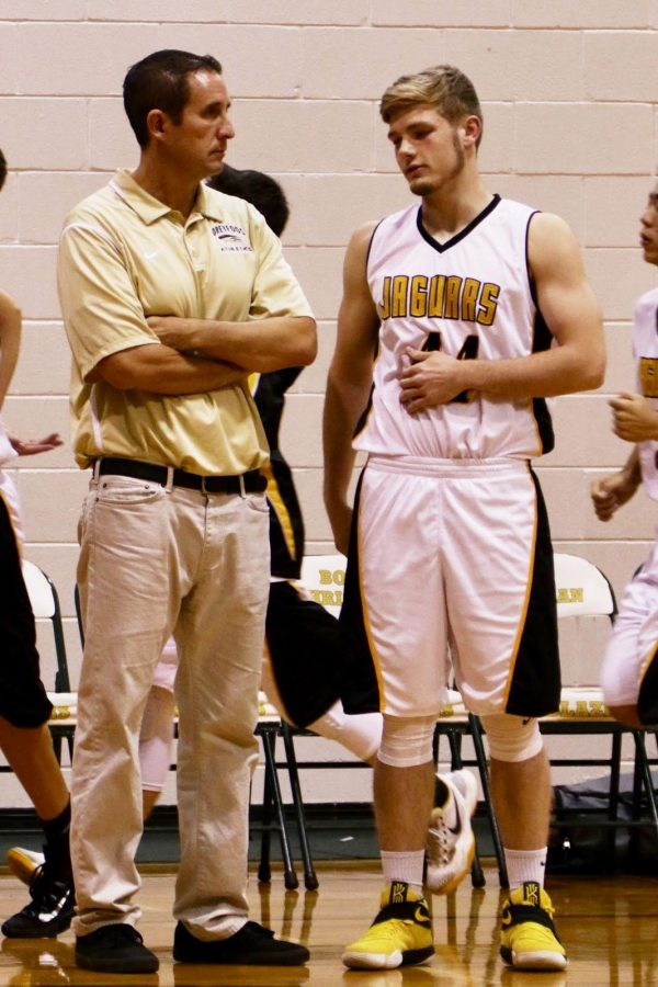 Starting forward and visual junior Aaron Crawford stands alongside basketball coach and history teacher Jeffrey Stohr at a basketball game prior to his season-ending injury.