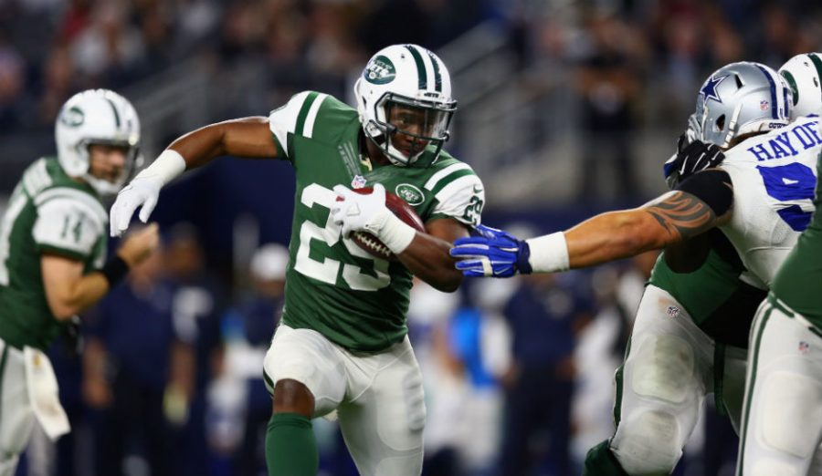 New York Jets running back Bilal Powell carries the ball as he outruns the defense.