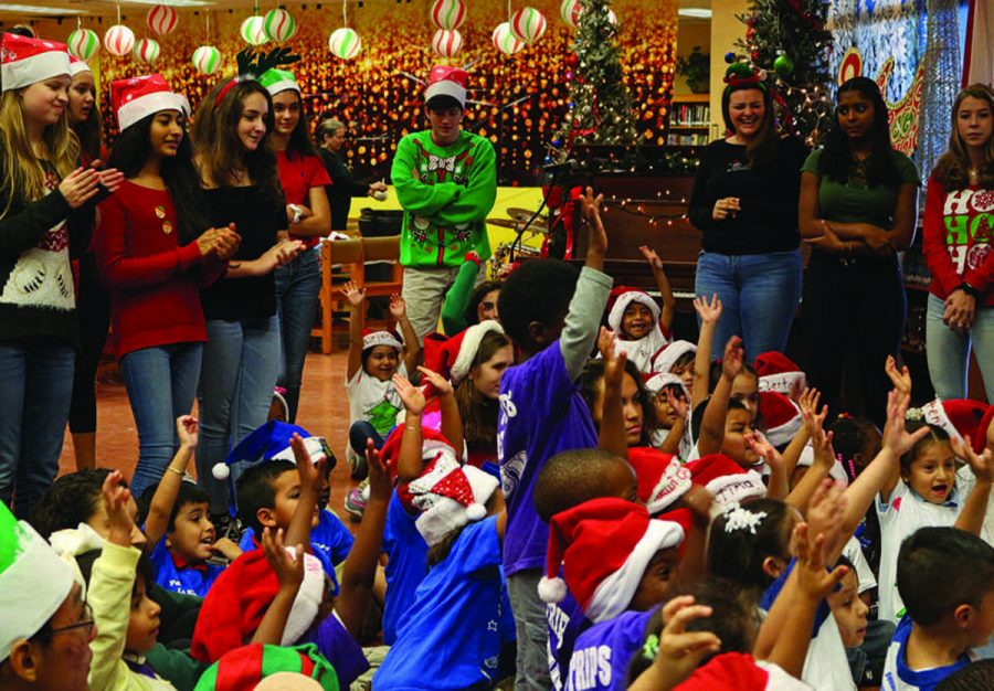 Children in attendance at A.R.T.S. Club's annual Jefferson Jubilee excitedly raise their hands as they were greeted by Santa, who came to the event bearing gifts for each of them.