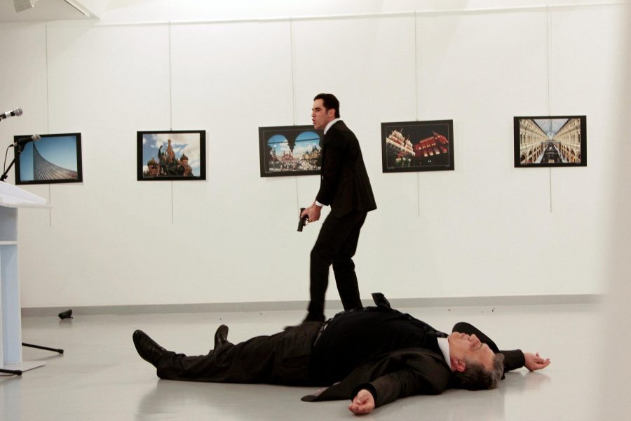 Attacker Mevlut Mert Altintas after the shooting of Russian ambassador Andrei Karlov, who lies on the floor, on Monday, Dec. 19 at a gallery in Ankara, Turkey.