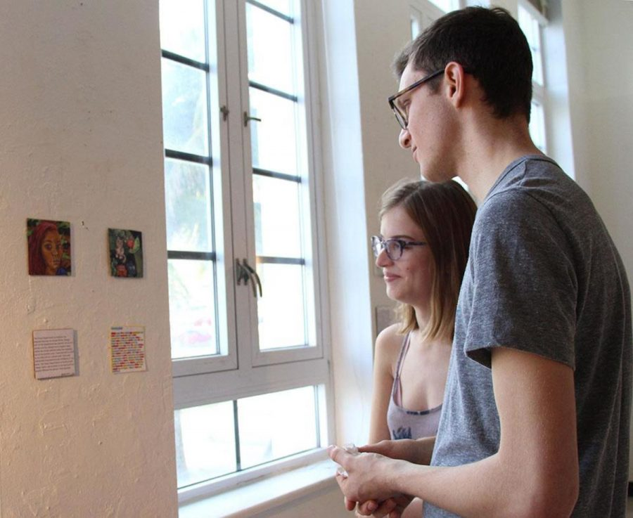 Visual senior Bailey Triggs and communications senior Matt Nadel view the art presented in the 4x4 Show held in the Building 9 gallery on Jan. 17.