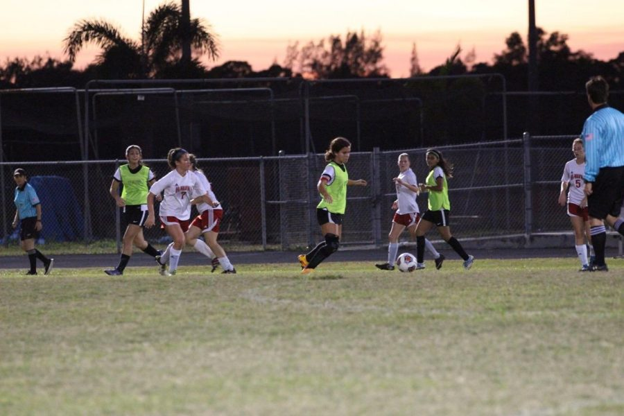 Strings senior and team captain Sarah King heads toward the ball to receive a pass from her teammates while surrounded by girls from the opposing team.