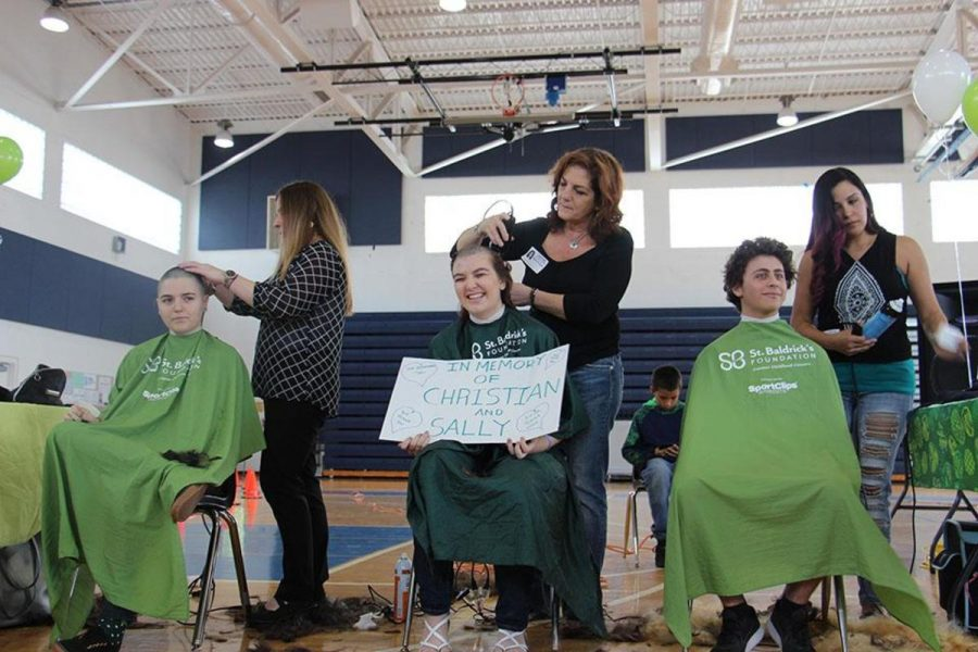 Visual sophomore Bridget Amico, communications junior Gina Givens, and theatre junior Ethan Izenwasser sit and get their head shaved at the annual St. Baldrick's event held on Feb. 9 in the gym.
