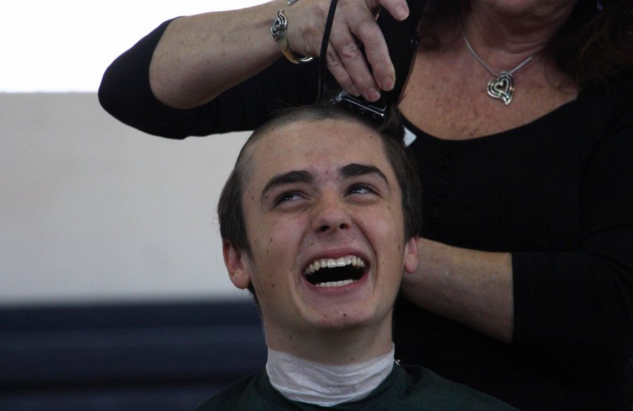 Communications junior Garret O'Donnell smiles as his head is shaved for St. Baldrick's